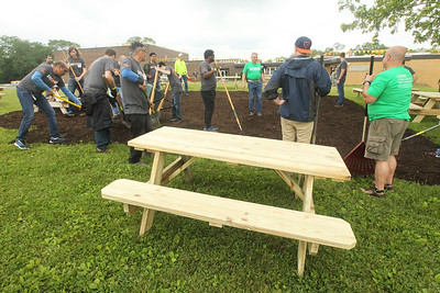 Candace H. Johnson-For Shaw Media Volunteers work on mulching an area to put picnic tables on for kids to eat their lunch outside in the back of the school during the Discover Business Technology and Volunteer Day at Gavin South Middle School in Ingleside. Over 500 volunteers from Discover Financial Services came to Gavin South to help at the event. (6/20/19)