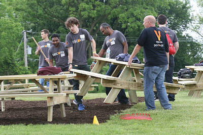 Candace H. Johnson-For Shaw Media Volunteers from Discover Financial Services move picnic tables to their right spots after mulching a section in the back of the school during the Discover Business Technology and Volunteer Day at Gavin South Middle School in Ingleside. Twenty-four picnic tables were made so students would have a place to eat lunch outside. (6/20/19)