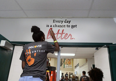 Candace H. Johnson-For Shaw Media Kiarra Pratchett, of Gary, Ind., paints a mural at the entrance to the gym during the Discover Business Technology and Volunteer Day at Gavin South Middle School in Ingleside. Over 500 volunteers from Discover Financial Services came to Gavin South to help at the event. (6/20/19)