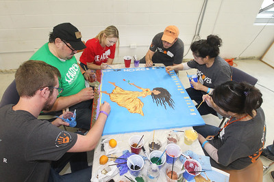 Candace H. Johnson-For Shaw Media Volunteers paint a mural for the school library during the Discover Business Technology and Volunteer Day at Gavin South Middle School in Ingleside. Over 500 volunteers from Discover Financial Services came to Gavin South to help at the event. (6/20/19)