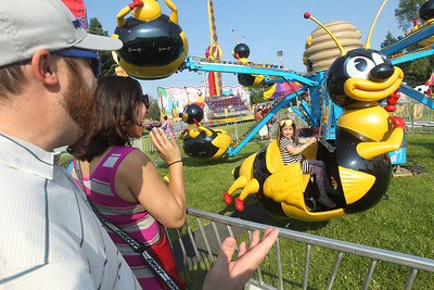 Candace H. Johnson-For Shaw Media Jeff and Sara Schmidt, of Barrington wave to their daughter, Ariya, 5, as she rides on the Bumble Bee Bop during the Island Lake Carnival at Water Tower Park in Island Lake. (6/22/19)