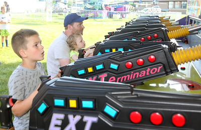 Candace H. Johnson-For Shaw Media Jonathan Reber, 8, of Taylorville, Joe Niedbalsky, of Island Lake and his daughter, Charlotte, 3, play the Bazooka Blaster game to win a prize during the Island Lake Carnival at Water Tower Park in Island Lake. (6/22/19)