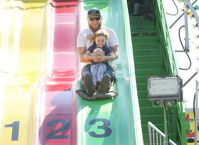 Candace H. Johnson-For Shaw Media Ryan Robinson, of McHenry and his daughter, Lily, 3, have fun going down the Power Slide during the Island Lake Carnival at Water Tower Park in Island Lake. (6/22/19)