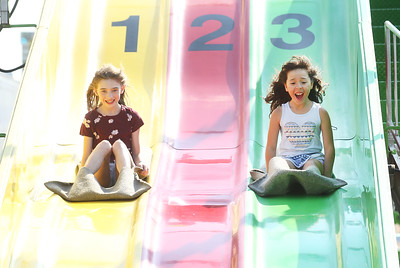 Candace H. Johnson-For Shaw Media Emma Mintun, 8, of Island Lake and Alyssia Aguilar, 9, of Des Plaines go down the Power Slide during the Island Lake Carnival at Water Tower Park in Island Lake. (6/22/19)