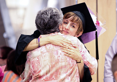 Michelle LaVigne/ For Shaw Media Tina Mengel of Lake in the Hills, gives a hug to her mother Pam Gianpicolo of Scarlet, NC., after the Spring Commencement at McHenry County College in Crystal Lake on Saturday, May 16, 2015. Mengel received her associates in criminal justice. Michelle LaVigne/ For Shaw Media