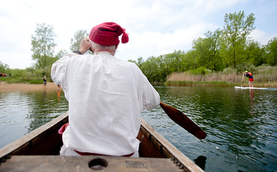 Michelle LaVigne/ For Shaw Media Don Mueggenborg of Lamont and with the wears his toque, a hat popular from the 13th to the 16th century in France, while he paddles on a voyageur canoe during the Paddle in the Park event in the Hollows Conversation Area in Cary on Saturday, May 16, 2015. Mueggenborg was a part of the Southwest brigade historical interpreters, who provided trips inside the voyageur to visitors as well as explaining the role of the canoe in early American settlement.