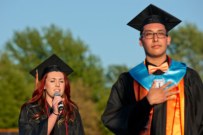 Michelle LaVigne/ For Shaw Media Jesus Varela stands by after giving the Pledge of Allegiance while Katelynn McManus sings the National Anthem during the McHenry High School-East Campus Commencement in McHenry on Thursday, May 21, 2015.