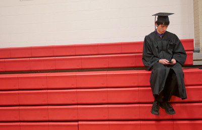 Michelle LaVigne/ For Shaw Media Nevada Perry of McHenry checks his phone before lining up for the McHenry High School-East Campus' Commencement in McHenry on Thursday, May 21, 2015.