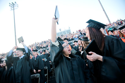 Michelle LaVigne/ For Shaw Media Megan Mae Brackenfield (right,) watches as Casey Lynn Bracken gives a victory cheer after the McHenry High School-East Campus Commencement in McHenry on Thursday, May 21, 2015.