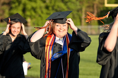 Michelle LaVigne/ For Shaw Media Abigail Wojcik secures her cap as she heads to her seat during McHenry High School-East Campus' Commencement in McHenry on Thursday, May 21, 2015.