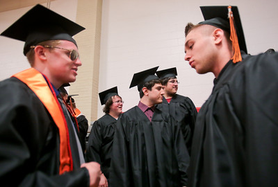 Michelle LaVigne/ For Shaw Media (Closest right,) Quinton Pilat of McHenry visits with Tom Schaade of McHenry (left,) while (background left to right,) Joe Tullar of McHenry, Andy Perez of Island Lake and Nathan Sell of Lakemoor all wait to line up for the McHenry High School-East Campus' Commencement in McHenry on Thursday, May 21, 2015.