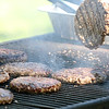 A burger is flipped on the grill during the Loyalty Day Picnic at the Batavia VFW May 7.