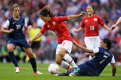 Japan's Yuki Ogimi is tackled by United States' Shannon Boxx in front of United States' Carli Lloyd (10) during the women's soccer gold medal match at the 2012 Summer Olympics, Thursday, Aug. 9, 2012, in London. (AP Photo/Lefteris Pitarakis)