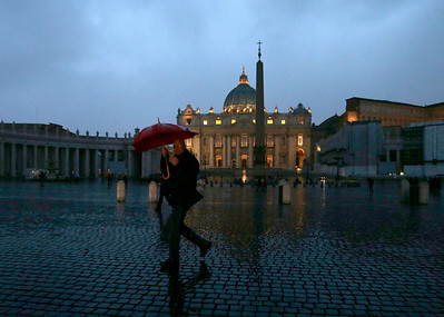 A man holds an umbrella under heavy rain as he walks in St. Peter's Square at The Vatican, Monday, Feb. 11, 2013. Declaring that he lacks the strength to do his job, Pope Benedict XVI announced Monday, Feb. 11, 2013 he will resign Feb. 28, becoming the first pontiff to step down in 600 years. His decision sets the stage for a mid-March conclave to elect a new leader for a Roman Catholic Church in deep turmoil. (AP Photo/Alessandra Tarantino)