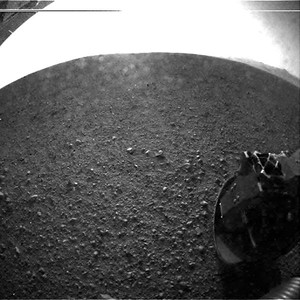 This photo provided by NASA's Jet Propulsion Laboratory shows the gravel on the surface of Mars' Gale Crater where the Curiosity rover landed late Sunday, Aug. 5, 2012. On the horizon is the rim of the crater. Part of the spring that released the lens' dust cover can be seen at the bottom right, near the rover's wheel. At top left is part of the rover's power supply. The lines across the top are an artifact from the sensor since the camera is looking into the sun. (AP Photo/NASA/JPL-Caltech)