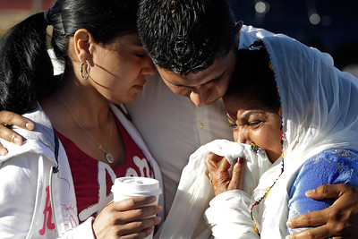 Amardeep Kaleka, son of the president of the Sikh Temple of Wisconsin, center, comforts members of the temple, Monday, Aug. 6, 2012, in Oak Creek, Wis., where a gunman killed six people a day earlier, before being shot and killed himself by police. Satwant Kaleka, 65, founder and president of the temple, died in the shooting. He was among four priests who died. (AP Photo/M. Spencer Green)