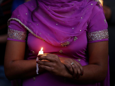 A woman takes part in a candle light vigil for the victims of the Sikh Temple of Wisconsin shooting Sunday, Aug. 5, 2012, in Milwaukee. An unidentified gunman killed six people at the suburban Milwaukee temple on Sunday in a rampage that left terrified congregants hiding in closets and others texting friends outside for help. The suspect was killed outside the temple in a shootout with police officers. (AP Photo/Jeffrey Phelps)