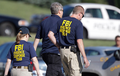 FBI agents walk the perimeter of a Sikh Temple, Sunday, Aug. 5, 2012, in Oak Creek, Wisc. An unidentified gunman killed six people at the temple in suburban Milwaukee in a rampage that left terrified congregants hiding in closets and others texting friends outside for help. The suspect was killed outside the temple in a shootout with police officers.(AP Photo/M. Spencer Green)