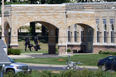 A police k-9 unit, left, and a robot, center, are outside The Sikh Temple in Oak Creek, Wis., where a shooting took place Sunday, Aug 5, 2012. At least six people were killed Sunday when a gunman opened fire at the Milwaukee-area temple, and the suspected shooter later died in an exchange of gunfire with police, authorities said. (AP Photo/Jeffrey Phelps)
