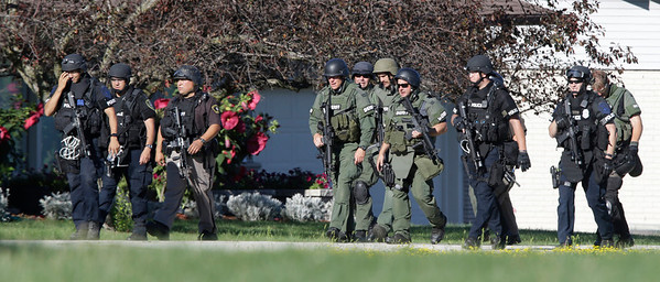 Police personnel walk away from the Sikh Temple of Wisconsin in Oak Creek, Wis., after a shooting Sunday, Aug 5, 2012. A gunman killed six people at the suburban Milwaukee temple in a rampage that left terrified congregants hiding in closets and others texting friends outside for help. The suspect was killed outside the temple in a shootout with police officers. (AP Photo/Jeffrey Phelps)