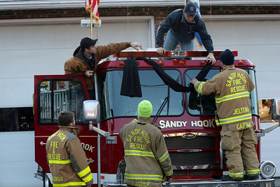 Sandy Hook firefighters hang bunting on their firetruck, Saturday, Dec. 15, 2012 in Sandy Hook village of Newtown, Conn.   The massacre of 26 children and adults at Sandy Hook Elementary school elicited horror and soul-searching around the world even as it raised more basic questions about why the gunman, would have been driven to such a crime and how he chose his victims.  (AP Photo/Mary Altaffer)