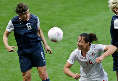 United States' and Crystal Lake native Amy LePeilbet, left, and Canada's Melissa Tancredi, center, try to head the ball during a semifinal women's soccer match at the 2012 Summer Olympics, Monday, Aug. 6, 2012, at Old Trafford in Manchester, England. (AP Photo/Ben Curtis)