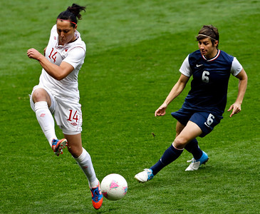 Canada's Melissa Tancredi, left, and United States' Amy LePeilbet, a Crystal Lake native right, challenge for the ball during the semifinal women's soccer match between the USA and Canada in the 2012 Summer Olympics, Monday, Aug. 6, 2012, at Old Trafford in Manchester, England. (AP Photo/Ben Curtis)