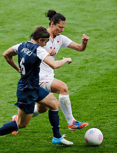Canada's Melissa Tancredi, right, and United States' and Crystal Lake native Amy LePeilbet, left, vie for the ball during their semifinal women's soccer match at the 2012 Summer Olympics, Monday, Aug. 6, 2012, at Old Trafford in Manchester, England. (AP Photo/Ben Curtis)