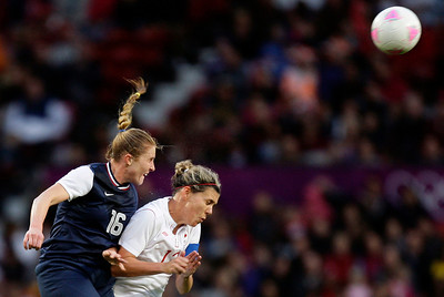 United States' Rachel Buehler, left, jumps for the ball against Canada's Christine Sinclair during their semfinal women's soccer match at the 2012 London Summer Olympics, Monday, Aug. 6, 2012 at Old Trafford Stadium in Manchester, England. (AP Photo/Jon Super)