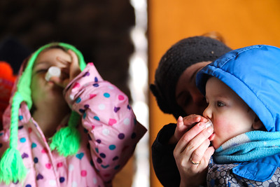 Jenny Kane - jkane@shawmedia.com Jenny Vogt feeds a sample of maple syrup to her son Adam Vogt, 2, while Katie Vogt, 7, (left) eats her sample during a tour at Festival of the Sugar Maples at Coral Woods Conservation Area in Marengo.The McHenry County Conservation District held the event.