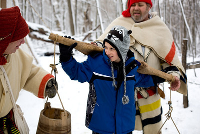 Jenny Kane - jkane@shawmedia.com Kyle Ochwat, 8, tries to hold an uneven yoke as McHenry County Conservation District volunteers John Carol, (left) and Dan MacKenzie, (right) talk about the origins of the maple syrup production at the annual Festival of the Sugar Maples in Marengo.