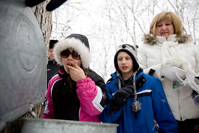 Jenny Kane - jkane@shawmedia.com McHenry County Conservation District volunteer Phil Vogrinc, of Woodstock, holds open a collection pale so that A.J. Paige, 9, (left), Kyle Ochwat, 8, (center) and Rita Dubas, (right) could taste the maple sap during the Festival of the Sugar Maples at Coral Woods Conservation Area in Marengo.