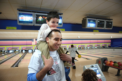 Daniel J. Murphy - dmurphy@shawmedia.com  Enrique Juarez of Crystal Lake holds his son Enrique, 2, (cq) during the annual Bowl for Kids Sake fundraiser for Big Brothers Big Sister of McHenry County Sunday March 4, 2012 at the Brunswick Zone in Algonquin.