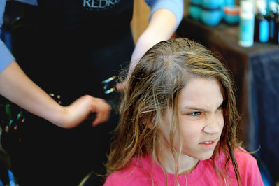 "Daniel J. Murphy - dmurphy@shawmedia.com  Conner Stevens, 11, of Cary winces as Caitlin Whitney of Crystal Lake cuts his hair Tuesday March 13, 2012 at International Hairways in Crystal Lake. Conner grew out his hair for over a year in order to donate it to Locks of Love on behalf of his godmother, Auntie ""Ju Ju"" Julie Mc Dillon who is a breast cancer survivor."