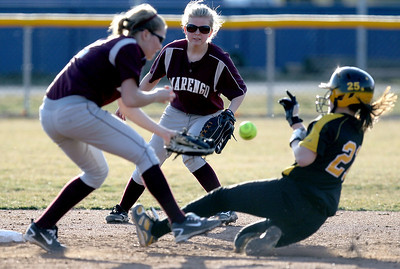 Sarah Nader - snader@shawmedia.com Marengo's Larissa Pfeiffer (center) watches as Marengo's short stop Shae Karsten tries to tag out Elmwood Park's Arianna Kelley at second base during Tuesday's season opener at Judson University on March 13, 2012. Marengo won, 3-1.