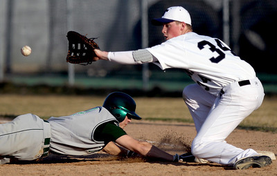 Sarah Nader - snader@shawmedia.com Cary-Grove's Andrew Brierton (right) waits for the ball while Fremd's Danny Haduch safely slides back to first during Thursday's season opener in Cary on March 15, 2012. Cary-Grove won, 11-5.