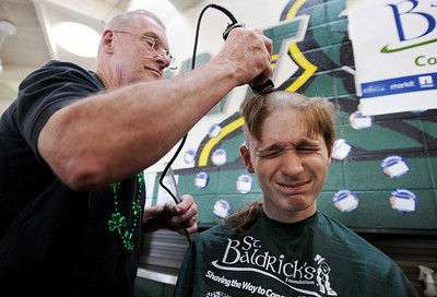Sarah Nader - snader@shawmedia.com Josh Brent, 15, of Crystal Lake gets his head shaved by volunteer Tony May (left) of Crystal Lake at Crystal Lake South High School to raise money for the St. Baldrick's Foundation on Friday, March 16, 2012. Brent had a brain tumor in 2005. He's going better, but still has to under go regular blood tests.