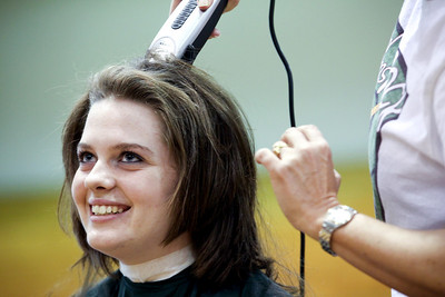 Jenny Kane - jkane@shawmedia.com Woodstock high school freshman Nora Brown gets her head shaved by Pattie Devinger, of Woodstock, during a St. Baldrick's Foundation fundraiser in the auditorium of the high school. Brown was best friends with Hope Fuller, who died of Diffuse Intrinsic Pontine Glioma, March 10, 2010 and would have been a freshman this year at Woodstock high school. St. Baldrick is a charity that raises money for childhood cancer research.