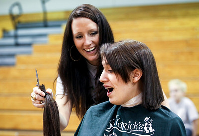 Jenny Kane - jkane@shawmedia.com Melissa Fuhler shows Woodstock high school junior Jelena Stojicuvic her cut off pony tail during a St. Baldrick's Foundation fundraiser. St. Baldrick is a charity that raises money for childhood cancer research.