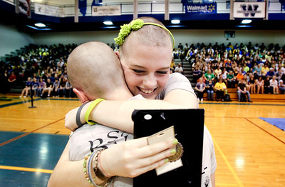 Jenny Kane - jkane@shawmedia.com Woodstock high school freshman Nora Brown holds a photo of herself and her best friend Hope Fuller as she hugs her friend Amanda Jandernoa after the two had their heads shaved during a St. Baldrick's Foundation fundraiser. Fuller died of Diffuse Intrinsic Pontine Glioma, March 10, 2010 and would have been a freshman this year at Woodstock high school. St. Baldrick is a charity that raises money for childhood cancer research. Zach Stone raised the most money, netting $2,300 for the organization.