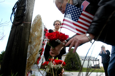 Jenny Kane - jkane@shawmedia.com Marcia Jarecki, (center) watches as John Johnson is puts flowers and a wreath at Galt Airport to commemorate those who lost their life in a mid air military plane explosion that killed 27 men and women on March 19, 1982. Jarecki's husband air-force TSgt. Kenneth Jarecki died in the crash. Marlene Lantz, (right), who was the Chief Deputy corner of McHenry County at the time of the crash watches from a distance.