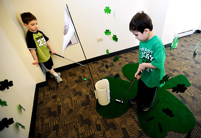 Sarah Nader - snader@shawmedia.com A.J. Valentine (left), 5, of Wheaton watches as his cousin, Andrew Dovidio, 5, of Woodstock finishes up the sixth hole during the 4th annual Mini-Links Golf Outing at Woodstock Public Library on Saturday, March 17, 2012. The library was transformed into an 18-hole miniature golf course cover all three level of the building. All proceeds went to benefit the Woodstock Public Library.