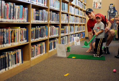 Sarah Nader - snader@shawmedia.com Matt Hedges (left) of Woodstock and Benjamin Weir, 3, of Woodstock watch as Elijah Hedges (center), 2, of Woodstock makes his first swing during the 4th annual Mini-Links Golf Outing at Woodstock Public Library on Saturday, March 17, 2012. The library was transformed into an 18-hole miniature golf course cover all three level of the building. All proceeds went to benefit the Woodstock Public Library.