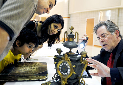 Sarah Nader - snader@shawmedia.com Roy Sucholeiki (left) of Elmhurst and his wife, Sharfi, and their son, Sammy, 8, listen as guest antique expert and appraiser Mark Moran appraises their French bronze clock during a special antique appraisal event at the Home and Garden Expo at Hampshire High School on Sunday, March 18, 2012. Moran estimated that the clock was worth $400-500.