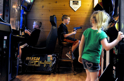 Sarah Nader - snader@shawmedia.com P.J. Weaver (left), 5, of Cary and his siblings, Ryan, 9, and Becca, 5, play video games while they wait for their pizza to arrive while having dinner at Nick's Pizza & Pub with their parents on Sunday, March 18, 2012.