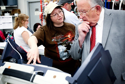 Jenny Kane - jkane@shawmedia.com Tues. March 20, 2012, Election Judge Rana Sundell-Adams shows Assistant Pastor Charles E. Miller, of Shepherd of the Hills Lutheran Church, how to vote on the AccuVote-TSX electronic voting machine at Bjorkman's Ace Hardware in McHenry.