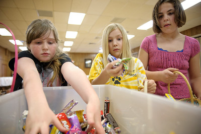 Daniel J. Murphy - dmurphy@shawmedia.com  Catie Reiser, 8, (left), Jennifer Heinberg, 9, (center), and Brooke Bertrand, 9, (right) assemble Easter baskets and decorated Easter bags that will be donated to the food pantries in Harvard and Marengo as well as Turning Point Domestic Violence Agency in Woodstock Wednesday March 21, 2012 in Marengo.