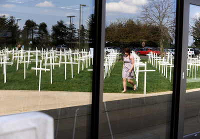 Sarah Nader - snader@shawmedia.com Maria Caravello, 19, of Richmond is reflected in the window while passing an exhibit that was put up at McHenry County College by the Students Supporting the Right to Life group as part the the student group's Right to Life Week on Wednesday, March 21, 2012. Each cross equals 20 babies lives lost each day in America by abortion.