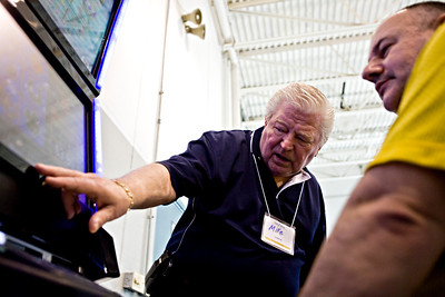 Lance Booth - lbooth@shawmedia.com Mike Rudowicz, of McCook, shows off a video gaming machine to Sam Abduloai, of Huntley, at Triple 7 in Lake in the Hills on Wednesday, March 21, 2012. Abduloai came to the expo at Triple 7 to look at the details to see what it would take to place one at Sammy's Bar.