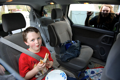 Daniel J. Murphy - dmurphy@shawmedia.com  Ben Hartman, 8, eats a sandwich in the car before his baseball practice Thursday March 22, 2012 in Wonder Lake. The Hartmann family is always on the go. They have four kids ranging from 8 to 16 and all participate in some sort of sport. To keep track of their busy schedule, the family has a color-coded calendar in their house.